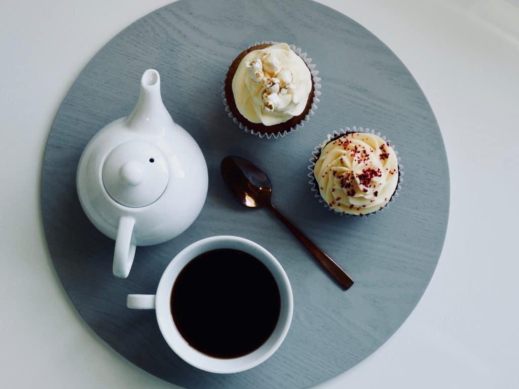Bandeja com um bule, uma xícara de café, uma colher e dois cupcakes.