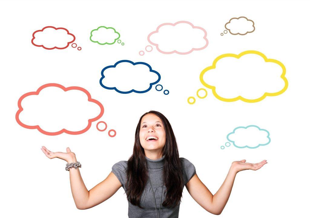 Imagem de uma jovem mulher vestindo uma blusa  cinza de lã de manga curta e gola rolê. Ela está com um semblante feliz e otimista. Ao fundo vários balões de pensamento coloridos.