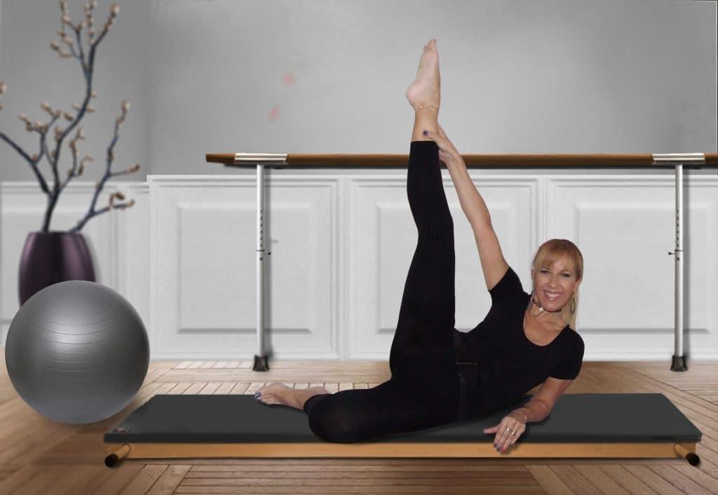 Mulher vestida de roupa de ginástica preta praticando pilatesem um estúdio. Ela está sentada sobre uma maca com capa preta, erguendo uma de suas pernas. Ao lado, uma bola de pilates na cor cinza.