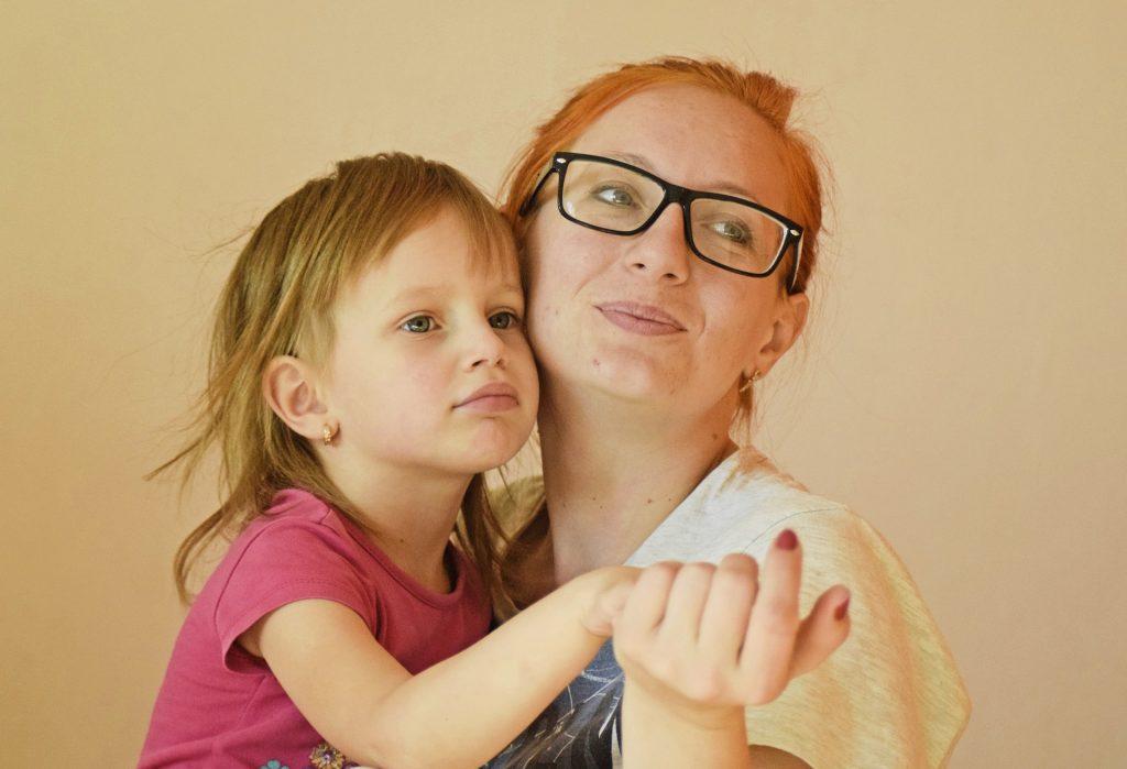 Imagem de mãe e filha. A mãe está com a criança no colo e segura a sua mão.