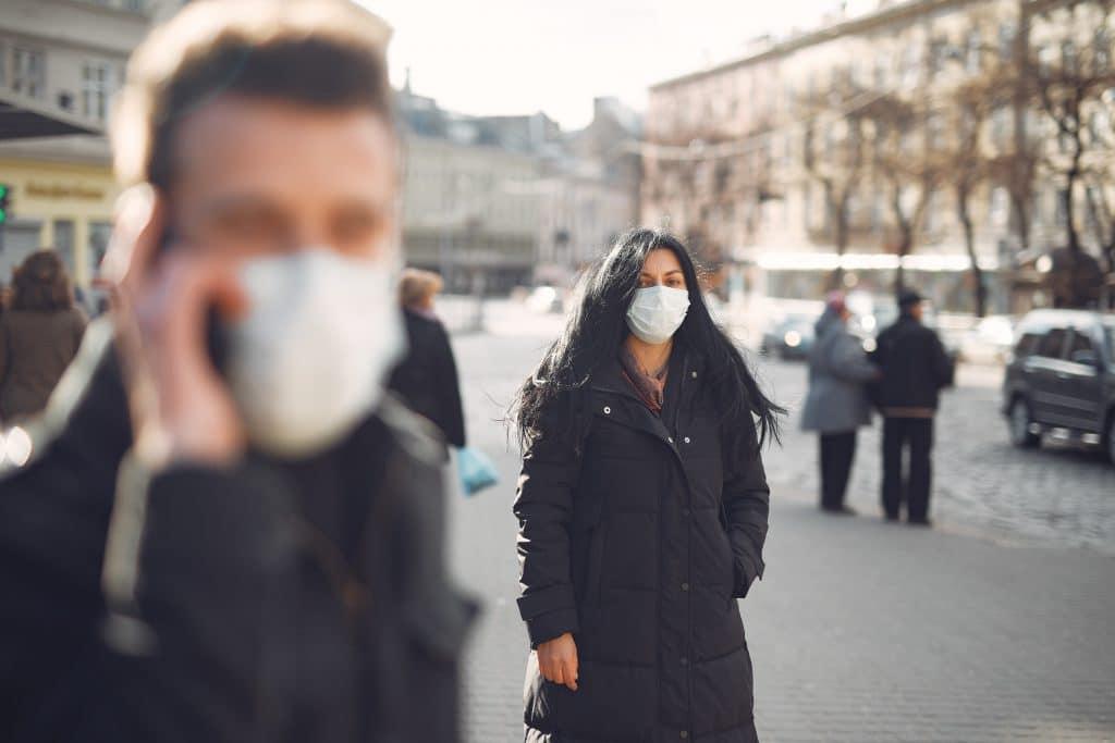 Pessoas usando máscaras na rua.