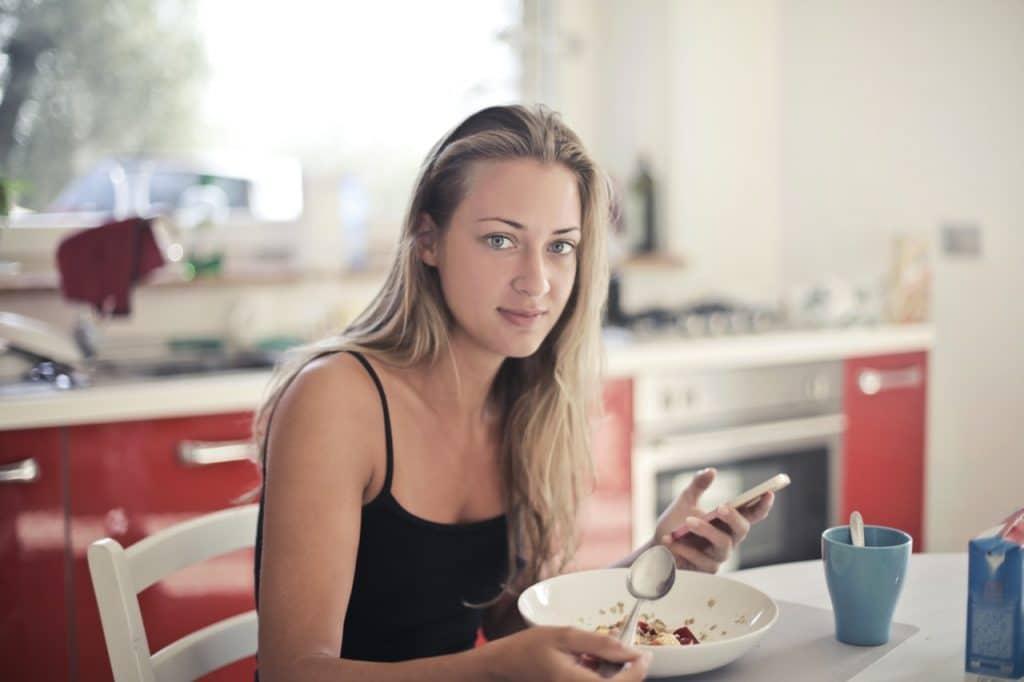 Mulher de cabelos lisos e roupas leves comendo cereal na cozinha de sua casa, enquanto olha para a câmera.
