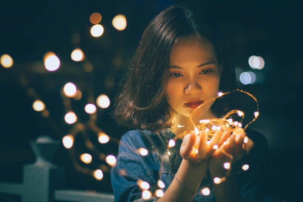 Garota segurando fio com luzes e luzes ao fundo embaçadas