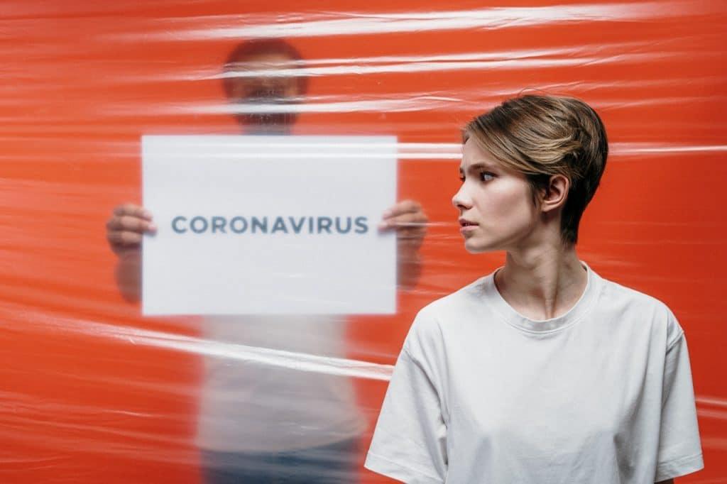 """Homem e mulher separados por divisória plástica transparente. A mulher está a frente, olhando para o lado, enquanto o homem está atrás do plástico, usando uma máscara de proteção e segurando uma placa escrito """"coronavírus"""""""