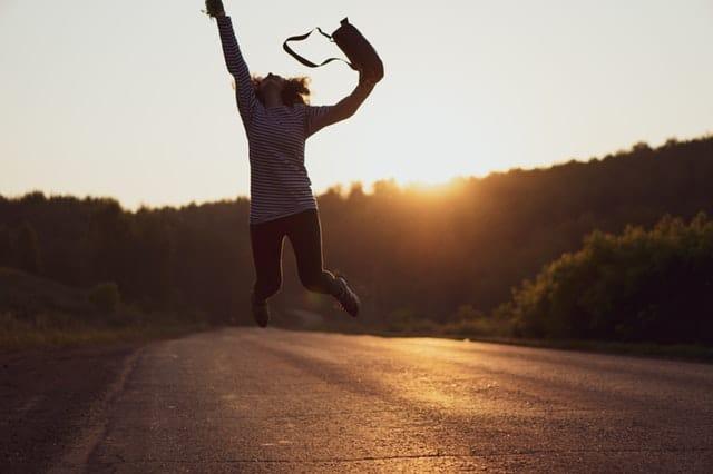 Mulher pulando em estrada com sol se pondo ao fundo