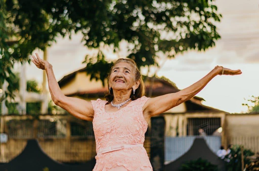 Mulher idosa de vestido sorrindo com as mãos para o alto, em uma rua, ao entardecer.