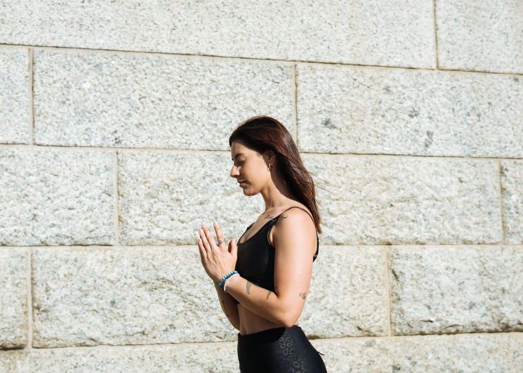 Mulher de perfil com mãos unidas em frente ao corpo e olhos fechados