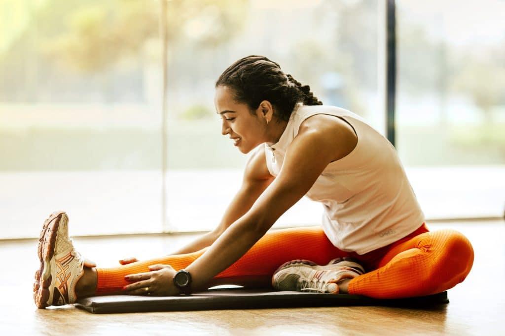 Mulher com roupas de ginástica sentada no chão, alongando-se.