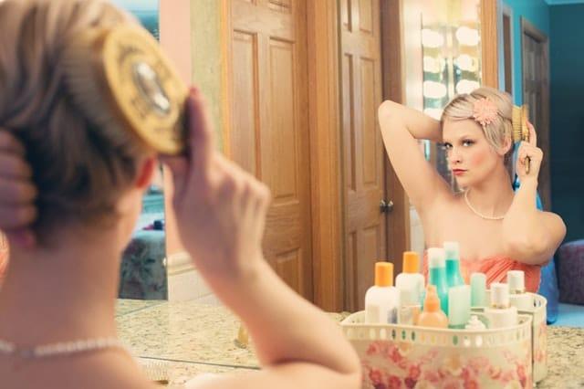 Mulher em frente ao espelho penteando cabelo