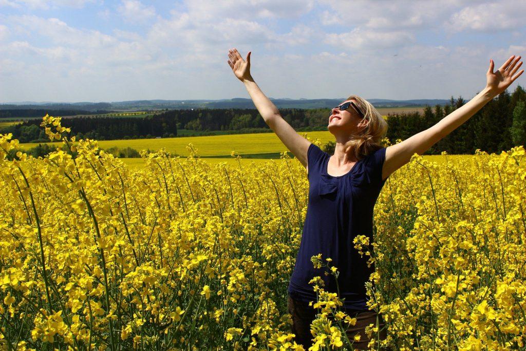 Mulher loira vestindo uma blusa azul marinho. Ela está em um campo de flores amarela. Ela está feliz com as mãos erguidas agradecendo ao universo.