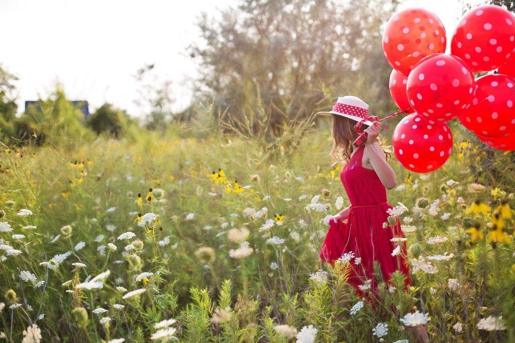 Linda mulher em um campo florido usando um vestido vermelho e um chapeu de palha bege com tecido vermelho de bolas brancas. Ela segura em suas mãos balões vermelhos.