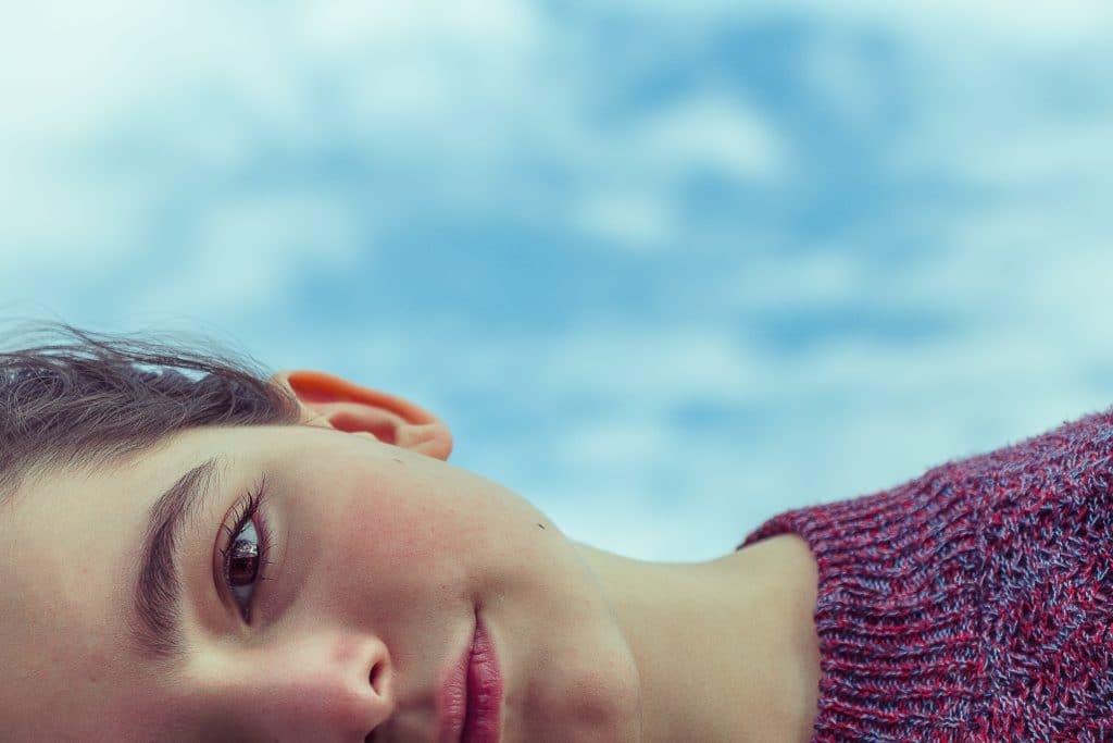 Metade do rosto de uma menina deitada, com aspecto sereno, usando uma blusa de lã.