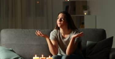 Mulher sentada no sofá, sob a luz de velas, olhando para cima com as mãos estendidas em sinal de oração