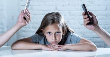 Mãe e pai segurando celular e criança sozinha
