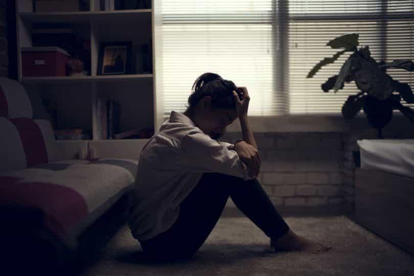 Mulher sentada no chão de sua sala encostada no sofá com cabeça baixa
