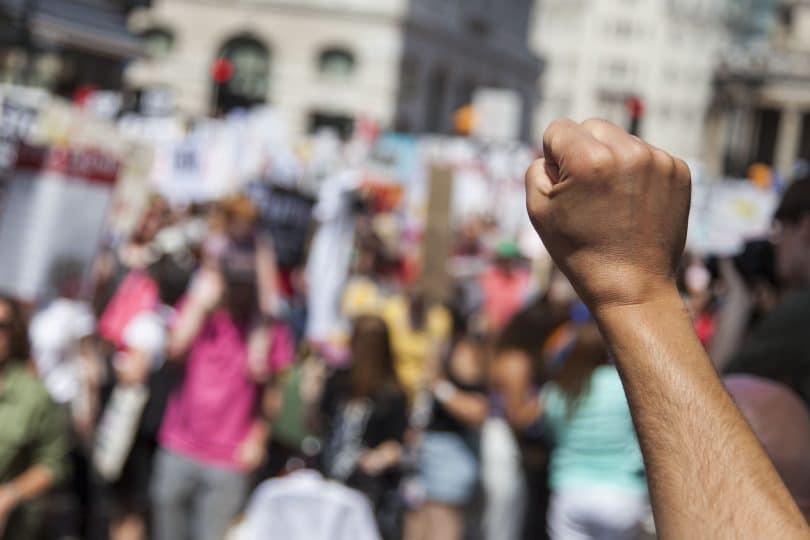 Pessoa de braço levantado e com a mão fechada com outras pessoas ao seu redor