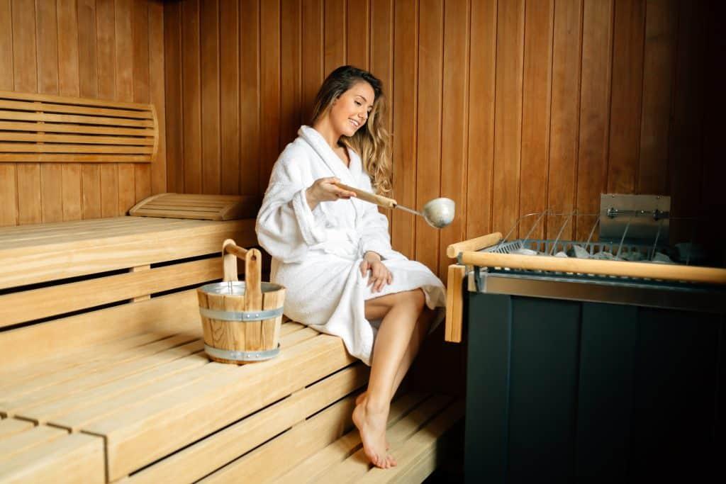 Mulher em um banheiro de roupão branco preparando o ritual da vaporização do útero.