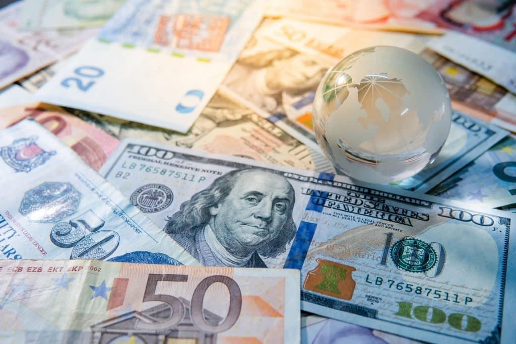 Vários tipo de dinheiro juntos com um cristal em formato do planeta terra