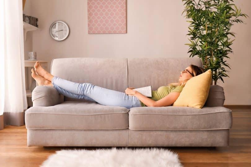 Mulher com os olhos fechados deitada no sofá com um livro aberto em sua barriga