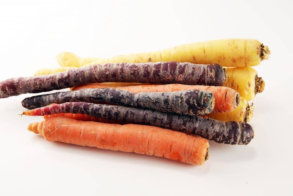 Imagem de cenouras de cores diferentes: amarela, laranja e roxa.