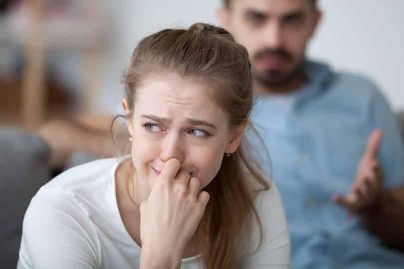 Mulher triste chorando com a mão sobre o rosto enquanto um homem a encara com expressão nervosa.