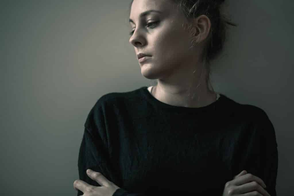 Mulher de braços cruzados com os olhos para baixo e com expressão de tristeza