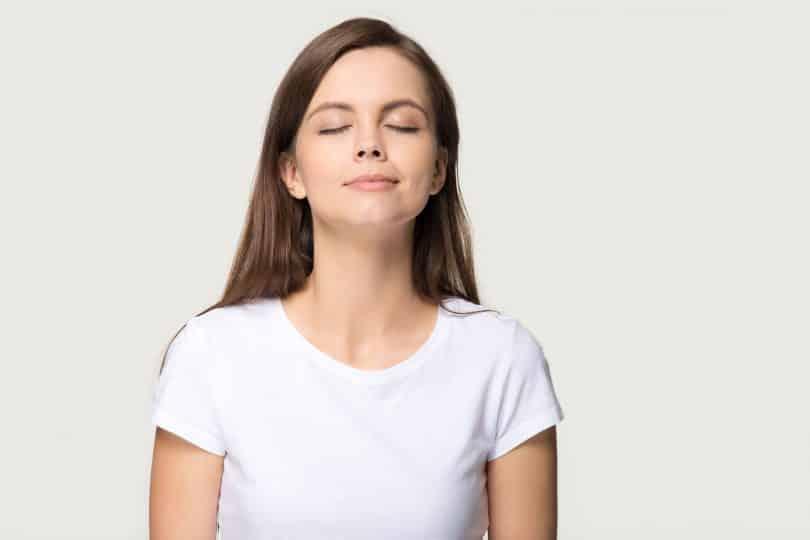 Mulher em pé, de olhos fechados e expressão tranquila.