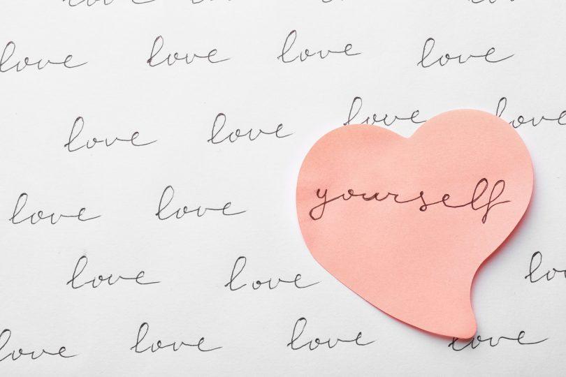 """Palavras """"love yourself"""" escritas em papéis."""