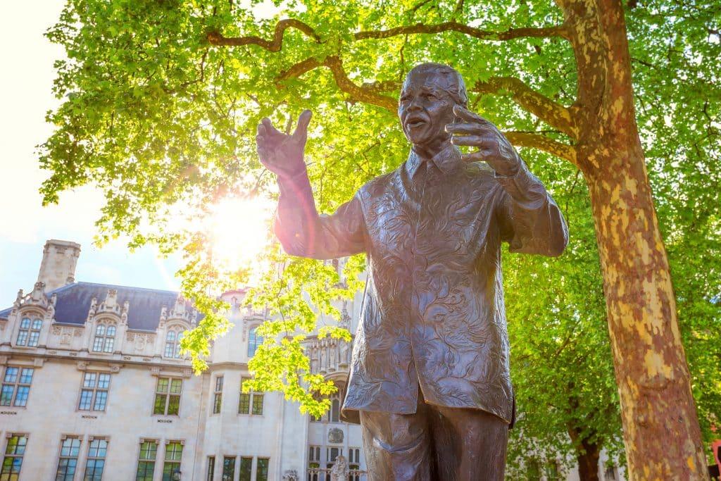 Imagem da estátua de Nelson Mandela sob a copa de uma linda árvore. Ao fundo um prédio antigo branco.