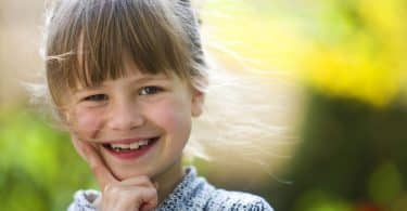 Menina pequena, com cabelo preso e franja na testa, sorrindo para a câmera.