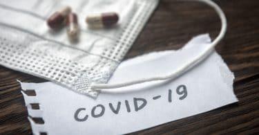 Máscara de proteção com alguns comprimidos e um bilhete escrito COVID-19