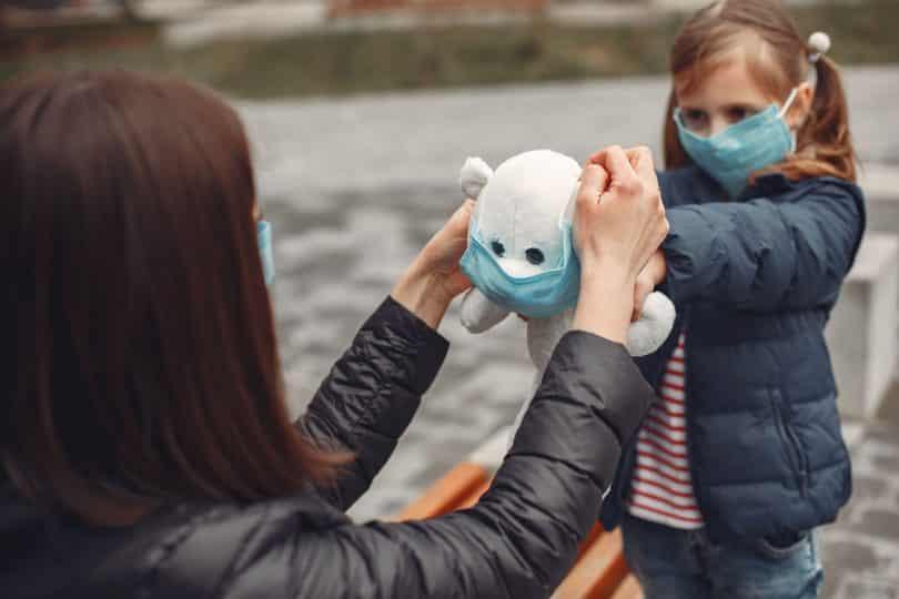 Mulher colocando uma máscara de proteção no ursinho de pelúcia de uma criança.