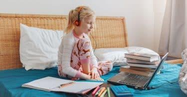 Menina sentada na cama com fones de ouvido olhando para um computador. Ao seu redor, tem-se livros, cadernos, canetas e uma calculadora.