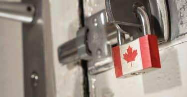 Porta trancada com fechadura de ferro, presa com um cadeado com a bandeira do Canadá.