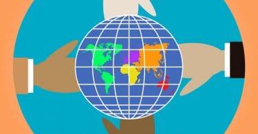 Desenho de quatro mãos de cores diferentes, segurando o planeta Terra.