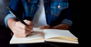 Imagem em detalhe de mulher escrevendo com lápis em um caderno. Ela usa camiseta e uma jaqueta jeans.