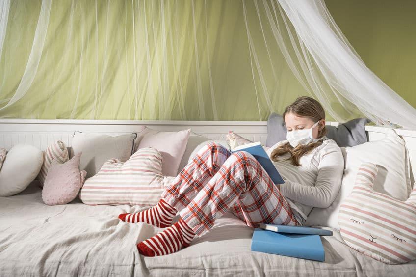 Menina usando máscara cirúrgica, sentada em cama com joelhos flexionados, lendo um livro.