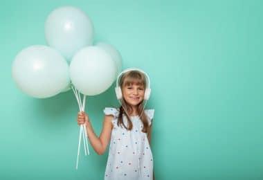Menina pequena com fones de ouvido e segurando balões.