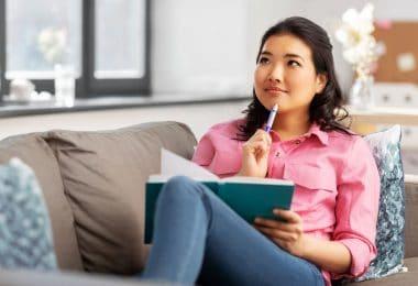 Mulher sentada em sofá e segurando caderno. Ela também segura uma caneta, que está encostada em seu queixo, com expressão pensativa.