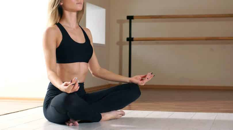 Mulher sentada no chão com as pernas cruzadas, meditando.