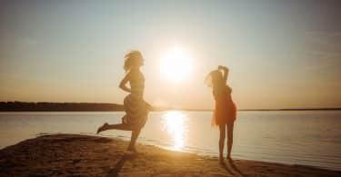 Mulher adulta e menina, ambas usando vestidos, pulando em praia durante o pôr do sol.