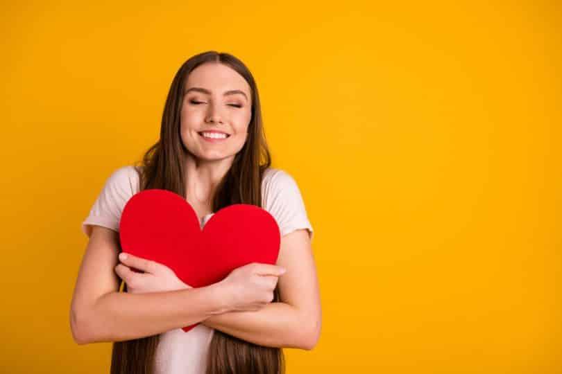 Mulher jovem, com os olhos fechados, sorrindo e abraçando um cartão vermelho grande em formato de coração.