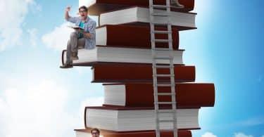 Livros empilhados, com uma escada encostada neles. Cada livro seria um andar, e um homem aparece sentado embaixo, no meio e no topo dos livros.