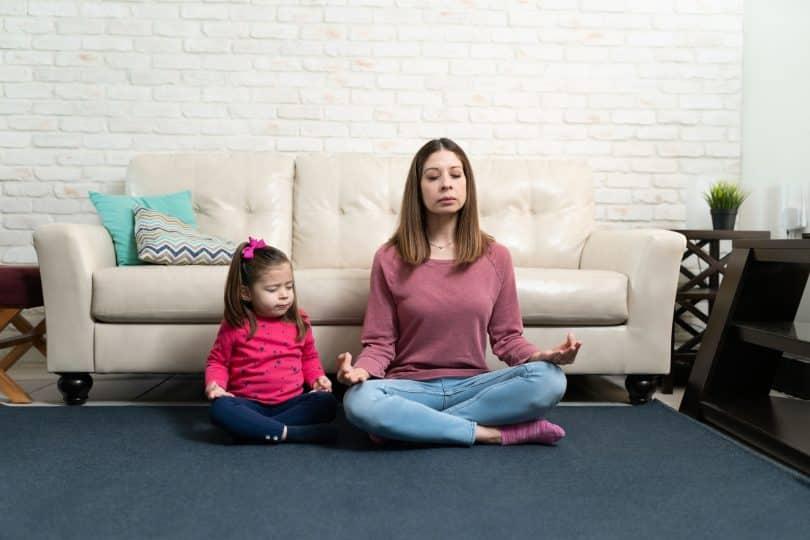 Mulher sentada no chão, encostada em sofá, meditando. Ao lado dela, uma menina pequena, imitando sua posição de meditação.