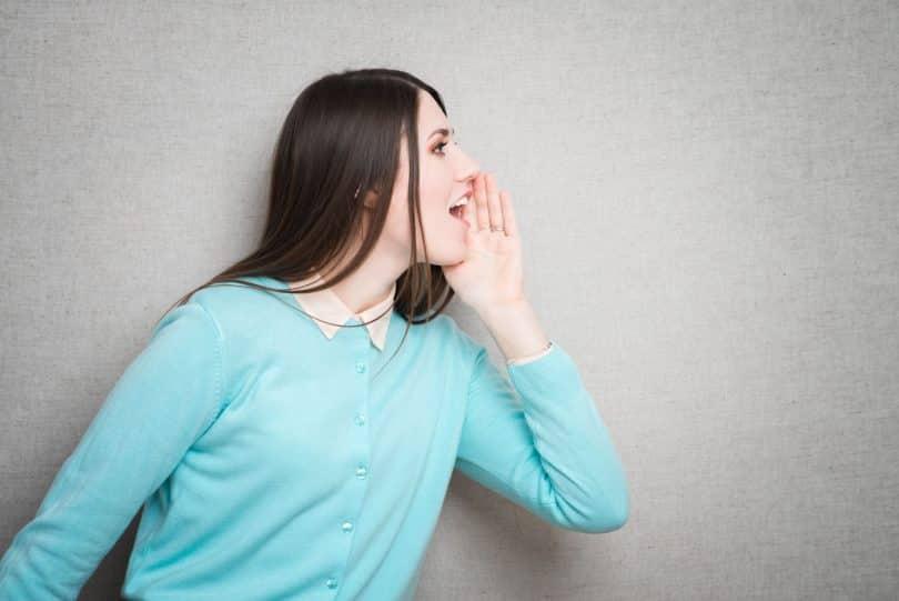 Mulher de perfil em frente a parede cinza, com uma mão encostada na parte do rosto mais distante da câmera, e com a boca aberta, como se estivesse gritando.