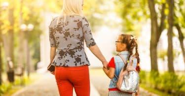 Menina pequena com cabelo preso e usando uma mochila nas costas, de mãos dadas com uma mulher. Elas estão andando, e de costas para a câmera.