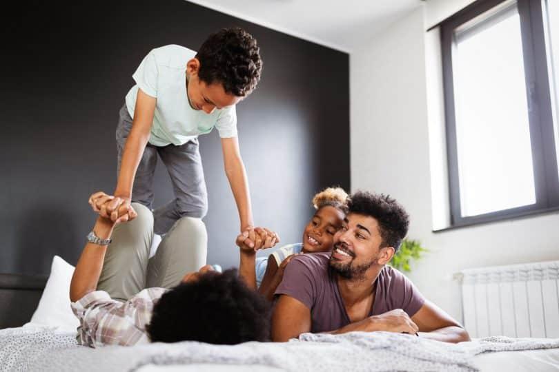 Família feliz em uma cama. Uma mulher está deitada de costas, com as pernas flexionadas, segurando as mãos e equilibrando um menino em suas pernas. Ao lado, uma menina deitada nas costas de um homem olham para a situação e dão risada.