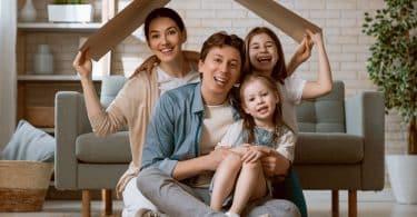 Família reunida em sala, segurando papelão sobre suas cabeças, simbolizando um telhado. Uma mulher e uma menina nas pontas seguram o papelão, com um homem e uma menina em seu colo no centro.