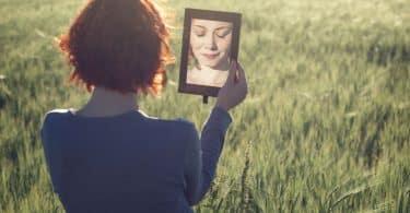 Mulher se olhando no espelho em um campo, durante o dia.