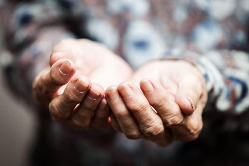 Pessoa com as mãos juntas abertas pedindo algo
